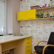 Письменный стол в детской комнате с навесной полкой для книг