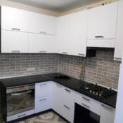 Угловая белая кухня с черной столешницей