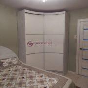 Угловой радиусный шкаф с кожанными вставками в спальне